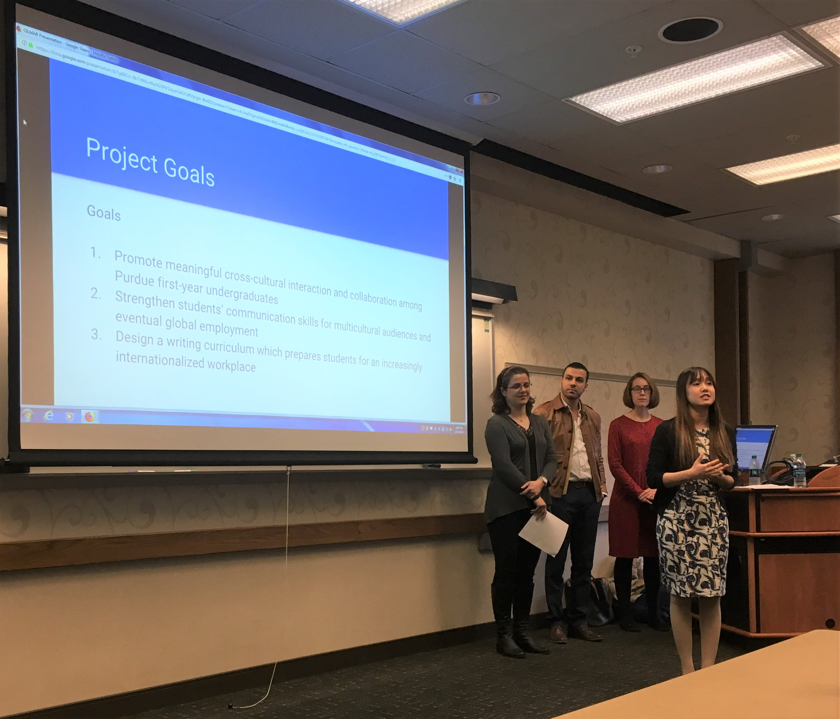 Research team presentation. Three team members standing and listening; Phuong speaking. PPT slide has the project goals displayed.